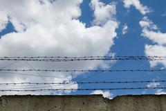 Barbed wire.concrete wall.clouds on blue sky.imprisonment. Stock Photos