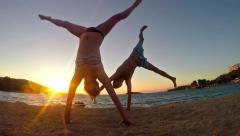 Two teen doing cartwheels on the sunset beach in slow motion Stock Footage