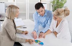 Young couple in a date with a banker or adviser for retirement arrangements. Stock Photos
