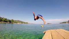 Slow motion of professional male swimmer jumping off the pier Stock Footage