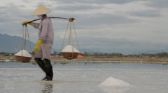 Workers carrying baskets filled with salt Stock Footage