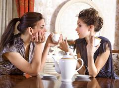 two pretty girl-friends drink tea - stock photo