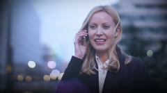 Young, attractive business woman talking on a mobile phone in the city Stock Footage