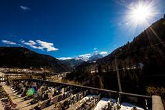 graveyard below a snowy alp peak in a sunny spring day - stock photo