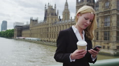 Young business woman on a smart phone, drinking coffee in London - stock footage