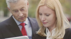 Professional businessman and businesswoman look at tablet and discuss content - stock footage