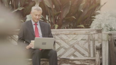 Businessman on laptop computer on a bench outside Stock Footage