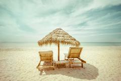 Tropical beach with thatch umbrella and chairs for relaxation Stock Photos