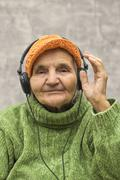 Stock Photo of elderly woman with headphones listening to music.