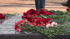 Red flowers at the monument. 4K. Stock Footage