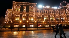 People walk by Red Square near GUM adorned with garlands. Stock Footage