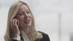 Happy, young, attractive business woman talking on a mobile phone in the city - stock footage