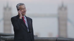 Smart business man on mobile phone in the city - stock footage