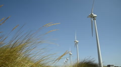 Windmills turning behind of grasses on a sunny day  Stock Footage