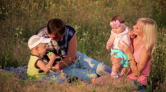 Stock Video Footage of Family rest in grass on picnic - happiness and smiling