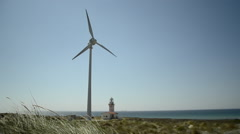 Single windmill and lighthouse on grassy land near sea on a sunny day  Stock Footage