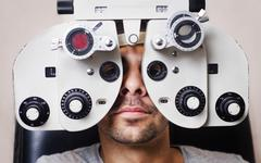 serious man in phoropter with eye calibration - stock photo