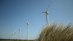 Windmills and grasses on strong wind on sunny day  Stock Footage