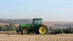 Agricultural tractor cultivating field Stock Footage