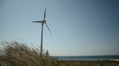 Lighthouse and windmill near sea on a sunny day Stock Footage