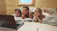 Three children laying in bed before sleeping and watching cartoons on laptop Stock Footage