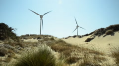 Two windmills turning behind of grassy and sandy land Stock Footage
