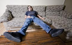 Tired man on sofa like a couch potato Stock Photos