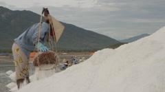 Worker Depositing Salt on Large Hill Stock Footage