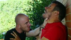Getting into fights: men using each other violence against a wall Stock Footage