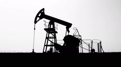 Dramatic Silhouette of working Oil Industry Pumpjack in the Field, Side Take Stock Footage