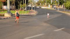 People walking and biking on empty city road Stock Footage