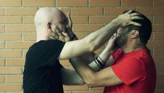Two men fighting against a wall: fight, quarrel. Slowmotion Stock Footage