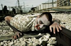 Zombie crawling by the railroad tracks Stock Photos