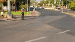 Man biking on deserted city road fastly Stock Footage