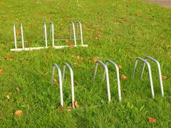 Public empty stand for bikes on grass. Gray iron frame with marks of corrosion. Stock Photos
