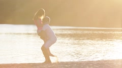 Couple in love plays and jumping near the river on sunset - stock footage