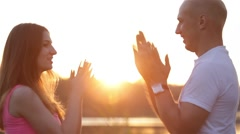 Couple plays Pat-a-Cake on sunset Stock Footage