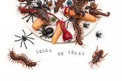 Trick or treat candy bugs spilling out onto white background Stock Photos
