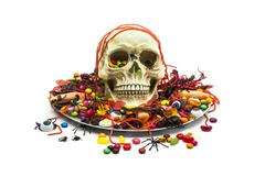 Trick or treat candy and skull in a candy dish Stock Photos