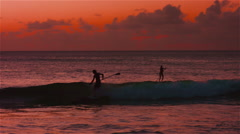 Paddle Boarder wipes out in the ocean at sunset in 4K Stock Footage