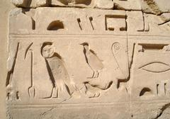 egyptian images and hieroglyphs engraved on stone - stock photo