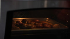 Oven open and woman pulls out roasted potatoes Stock Footage