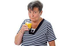 elderly woman drinking orange juice - stock photo