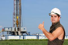 Oil worker thumb up and land drilling rig Stock Photos