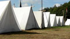 White block of tents - ground - forest (trees) - camp - sunny Stock Footage