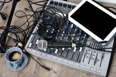 digital tablet placed on a audio mixer with a coffee - stock photo