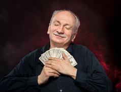 Old man holding dollar bills Stock Photos
