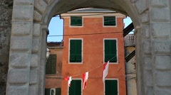 Europe Italy Liguria region city of Albenga 017 orange house behind town gate Stock Footage