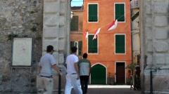 Europe Italy Liguria region city of Albenga 018 young guys go through city gate Stock Footage