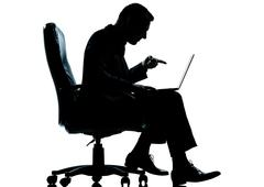 one business man computer computing sitting in armchair silhouette pointing - stock photo